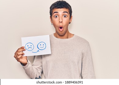 Young african amercian man holding sad to happy emotion paper scared and amazed with open mouth for surprise, disbelief face