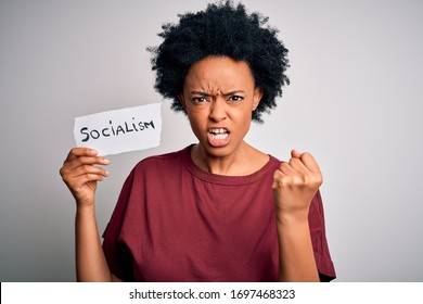Young African American afro politician woman with curly hair socialist party member annoyed and frustrated shouting with anger, crazy and yelling with raised hand, anger concept