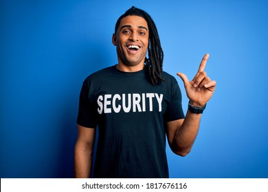 Young african american afro safeguard man with dreadlocks wearing security uniform surprised with an idea or question pointing finger with happy face, number one