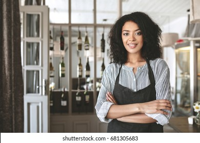 Young African American barista in apron standing with arms folded in restaurant. Nice girl with dark curly hair standing in apron at cafe. Portrait of smiling waitress looking at camera in uniform