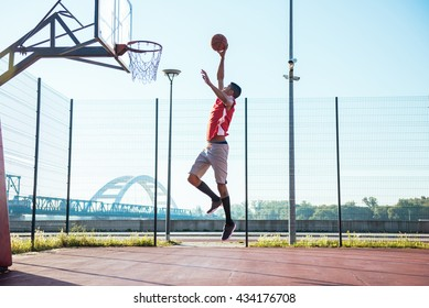 Young african american basketball player scoring a slam dunk.