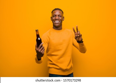 young african american black man against orange wall having a beer
