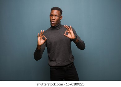 young african american black man feeling shocked, amazed and surprised, showing approval making okay sign with both hands against grunge wall