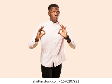 young african american black man feeling shocked, amazed and surprised, showing approval making okay sign with both hands against beige wall