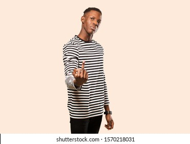 young african american black man feeling angry, annoyed, rebellious and aggressive, flipping the middle finger, fighting back against beige wall