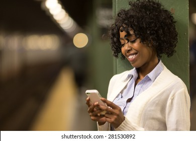 Young African American black woman texting on cell phone in subway station