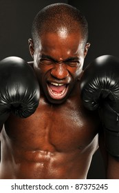Young African American Boxer screaming isolated on a dark background
