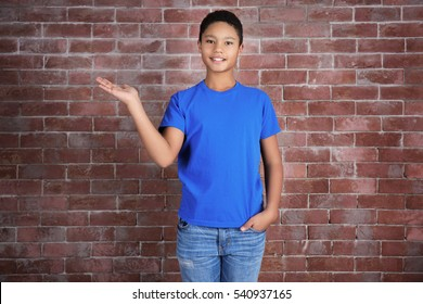 Young African American boy in blank blue t-shirt standing against brick wall