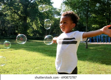 A young African American boy is looking at bubbles with his arms stretched out at the outdoor playground.