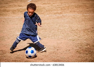 Young African American boy playing soccer.