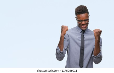 Young african american business man over isolated background very happy and excited doing winner gesture with arms raised, smiling and screaming for success. Celebration concept.