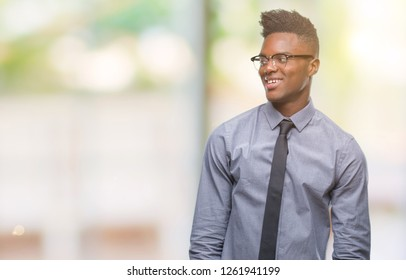 Young african american business man over isolated background looking away to side with smile on face, natural expression. Laughing confident.