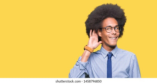 Young african american business man with afro hair wearing glasses smiling with hand over ear listening an hearing to rumor or gossip. Deafness concept.