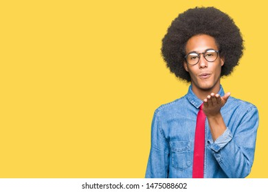Young african american business man with afro hair wearing glasses and red tie looking at the camera blowing a kiss with hand on air being lovely and sexy. Love expression.