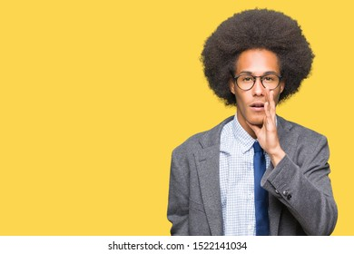 Young african american business man with afro hair wearing glasses hand on mouth telling secret rumor, whispering malicious talk conversation