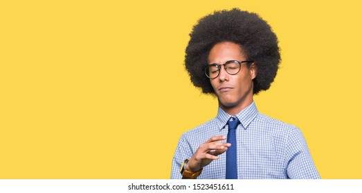 Young african american business man with afro hair wearing glasses disgusted expression, displeased and fearful doing disgust face because aversion reaction. With hands raised. Annoying concept.