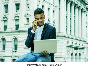 Young African American Business Man traveling, working in New York. Man sitting by vintage office building on street, reading, working on laptop computer, talking on cell phone. Color filtered effect.