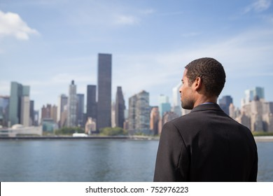 Young African American business man looking at NYC skyline, photographed in NYC in September 2017