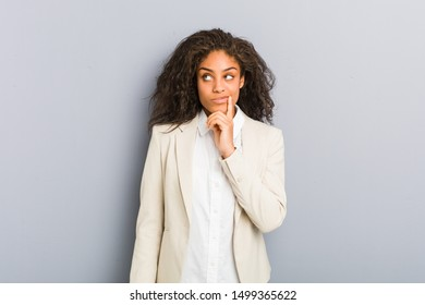 Young african american business woman looking sideways with doubtful and skeptical expression.