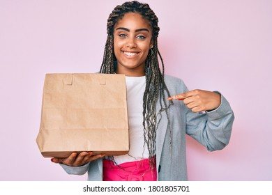 Young african american business woman with braids holding take away paper bag pointing finger to one self smiling happy and proud