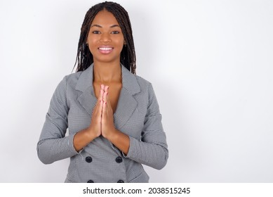 Young african american business woman with braids over white wall keeps palms together, has pleased expression. Glad attractive male makes request, pleads for mercy. Hopeful young adult.