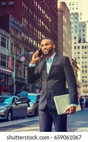 Young African American businessman with beard talking on cell phone, traveling in New York, wearing black suit, carrying laptop computer, walking on street in Manhattan. Cars, buildings on background.
