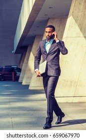 Young African American businessman with beard talking on cell phone, traveling, working in New York, wearing black suit, leather shoes, carrying laptop computer, walking out from office building.