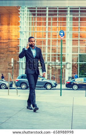 68295bd7f3 Young African American businessman with beard talking on cell phone,  traveling, working in New York, wearing black suit, leather shoes, carrying  laptop ...