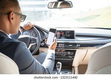 Young african american businessman driver wearing sunglasses sitting inside the car holding smartphone using navigation application driving view from the back seat