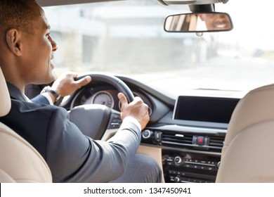 Young african american businessman driver sitting inside the car looking aside smiling cheerful view from the back seat