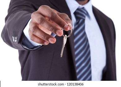 Young African American businessman holding a house key, isolated on white background