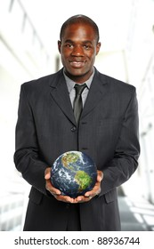 Young African American Businessman holding the earth inside an office building