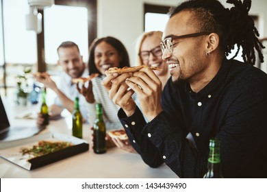 Young African American businessman laughing while sitting with colleagues in an office after work eating pizza and drinking a beer