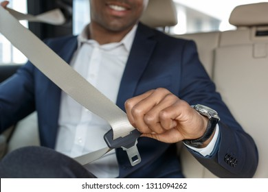 Young african american businessman sitting on the back seat in the car fastening seat belt close-up blurred background smiling cheerful