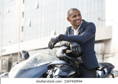 Young african american businessman sitting on motorcycle wearing sport gloves looking aside smiling happy