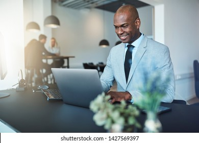 Young African American businessman smiling while sitting at his desk in an office working online with a laptop with coworkers in the background