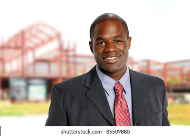 Young African American Businessman smiling with building construction on background
