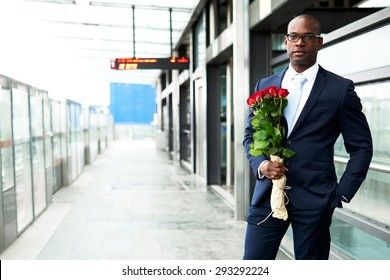 Young African American Businessman Standing at the Metro with Holding a Bouquet of Rose Flowers and Looking at the Camera.