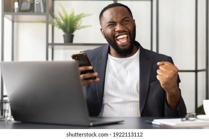 Junge afrikanische Geschäftsleute oder Studierende, die unerwartete gute Nachrichten auf dem Smartphone lesen