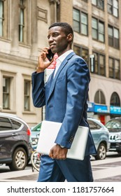 Young African American businessman talking on cell phone, traveling, working in New York, wearing blue suit, carrying laptop computer, walking on street in Manhattan. Cars, buildings on background.