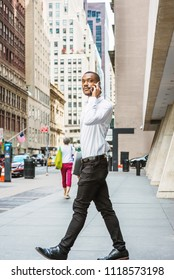 Young African American businessman traveling, working in New York, wearing white shirt, black pants, leather shoes, carrying laptop computer, walking out from office building, talking on cell phone,