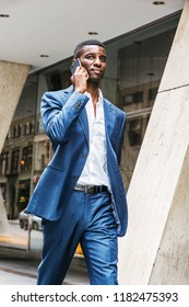 Young African American businessman traveling, working in New York, wearing blue suit, white shirt, walking on street outside office building, talking on cell phone. Glass window, columns on background