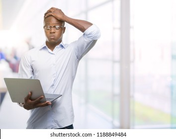 Young african american businessman using computer laptop stressed with hand on head, shocked with shame and surprise face, angry and frustrated. Fear and upset for mistake.