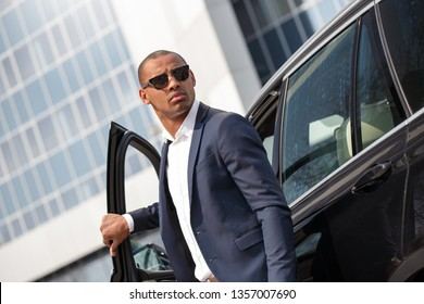 Young african american businessman wearing sunglasses standing holding opened door near car looking back cautious