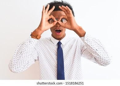 Young african american businessman wearing tie and glasses over isolated white background doing ok gesture like binoculars sticking tongue out, eyes looking through fingers. Crazy expression.