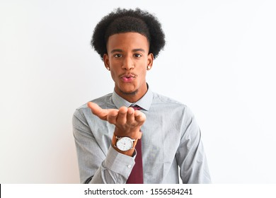 Young african american businessman wearing tie standing over isolated white background looking at the camera blowing a kiss with hand on air being lovely and sexy. Love expression.