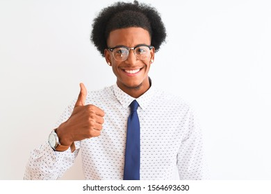 Young african american businessman wearing tie and glasses over isolated white background doing happy thumbs up gesture with hand. Approving expression looking at the camera showing success.