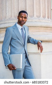 Young African American Businessman working in New York, wearing light gray suit, white undershirt, tie, wristwatch, holding laptop computer, standing by column outside office building, looking at you.