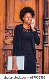 Young African American Businesswoman with afro hairstyle, wearing black fashionable clothes, holding laptop computer, standing by vintage office door in New York, talking on cell phone.