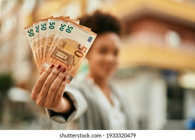 Young african american businesswoman holding 50 euro banknotes at the city.